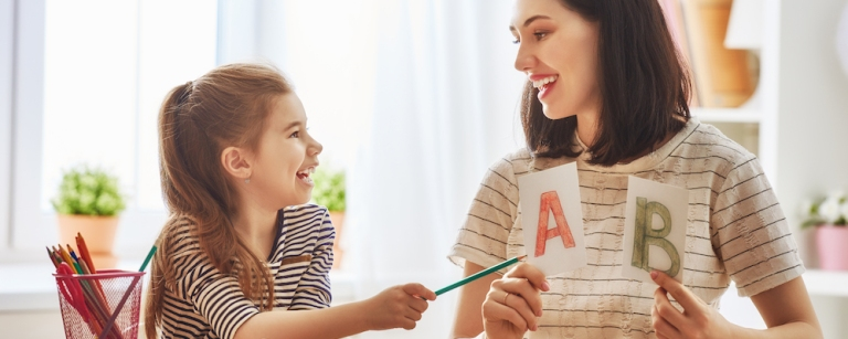 Happy family. Mother and daughter are learning to write. Adult woman teaches child the alphabet.